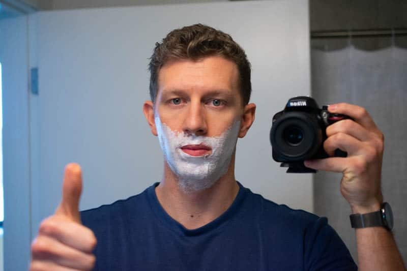 model with shaving cream on face giving thumbs up