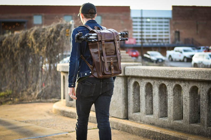 Model wearing leather rolltop backpack on bridge with hat