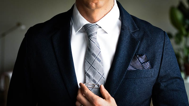 closeup of gentlemens collective tie on model paired with navy suit and white shirt