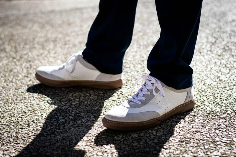 model backlit wearing white moral code brooks sneakers