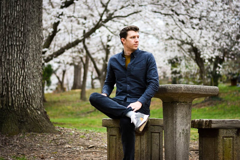 model sitting at bench with everlane tread sneakers blossoming trees in background