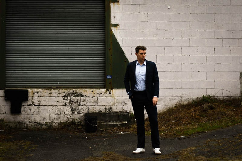 model standing wearing navy suit and white sneakers