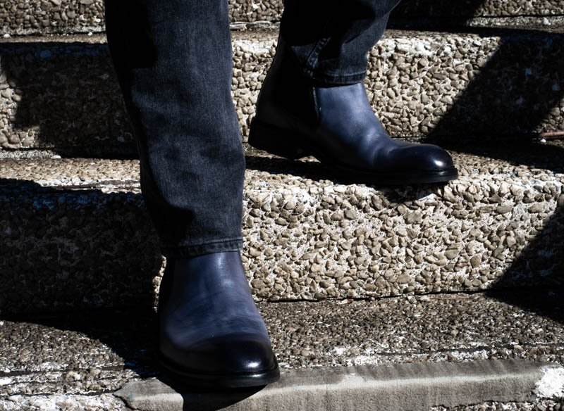 model wearing blue chelsea boots moral code on stair case
