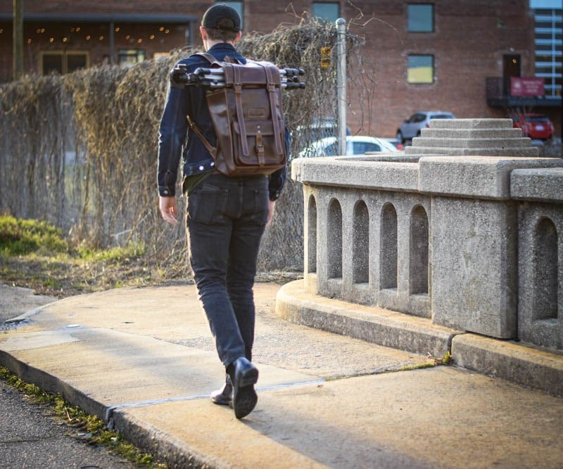model wearing moral code leather rolltop backpack and ice blue lawry chelsea boots walking on bridge during sunset