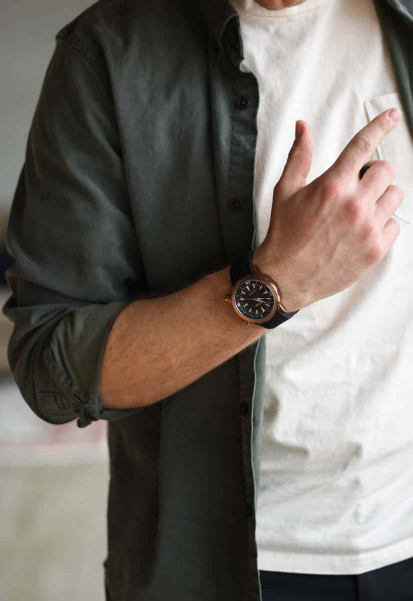 model wearing vincero vessel dive watch with green and white shirt