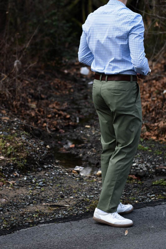 model with back turned to photographer wearing green chinos and blue dress shirt