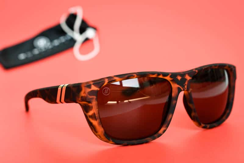 Blenders Eyewear charging lion sunglasses on red background