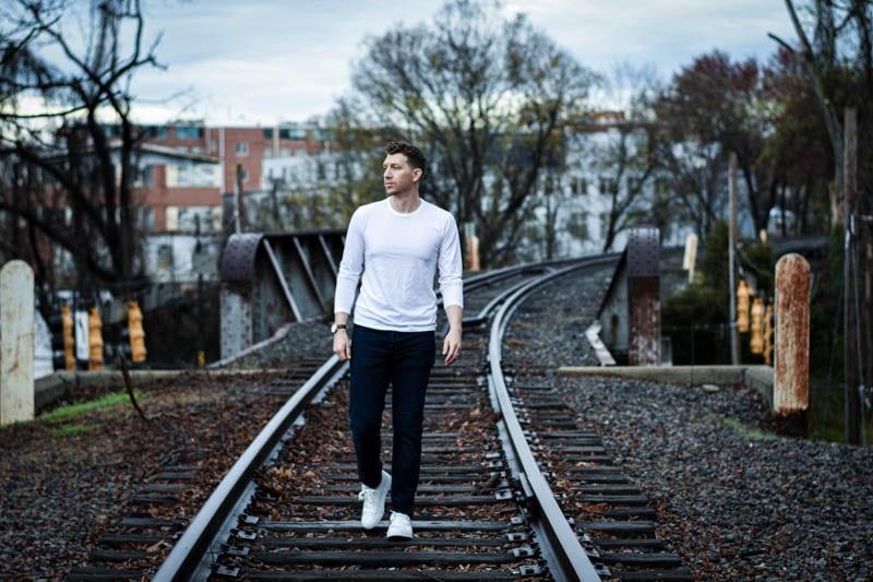 model in white rag and bone long sleeve shirt walking along train tracks