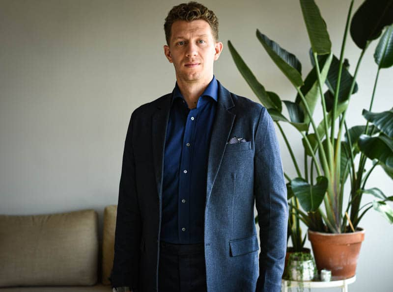 model wearing navy suit and dark blue shirt