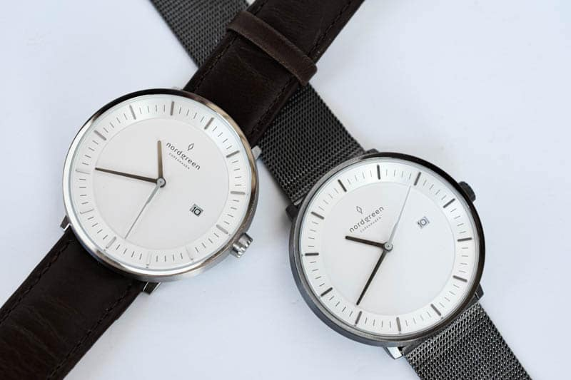 two nordgreen philosopher watches leather band steel mesh band overlap on white background
