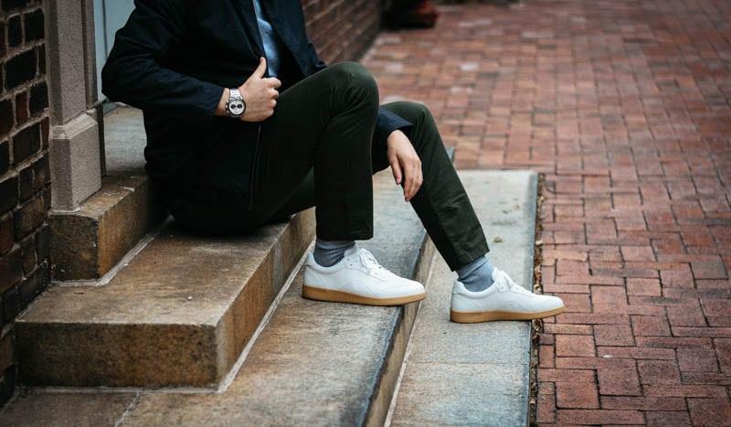 model adjusting black asket zip coat wearing olive asket chino everlane white tread sneaker and vincero apex racing watch