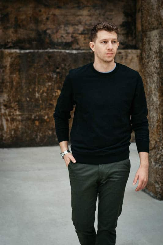model looking left with olive chinos and black crew neck sweater