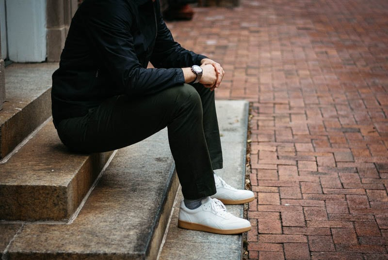 model sitting on concrete step with asket chino everlane tread white sneaker and vincero apex watch