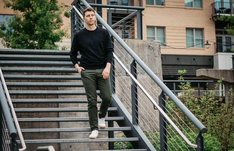 model walking down steel steps with olive asket chinos