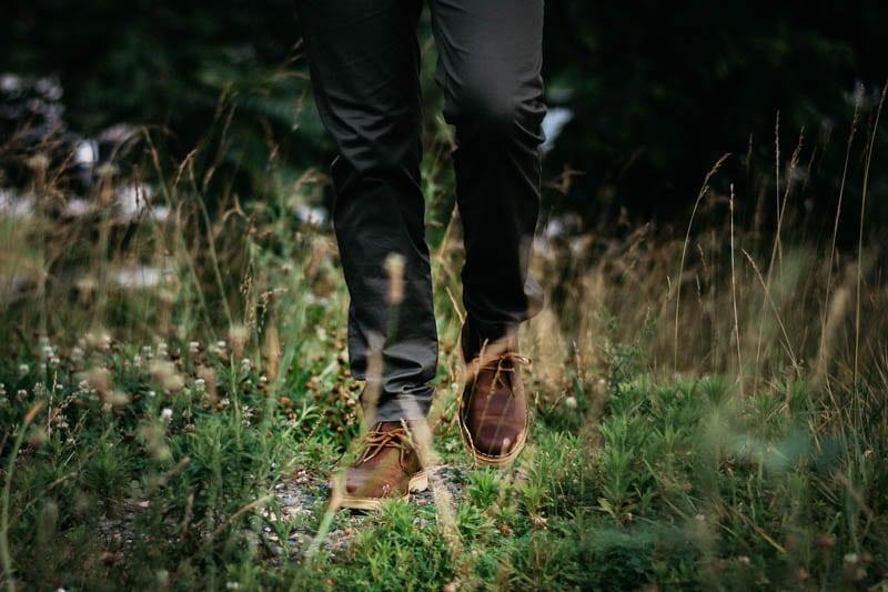 Model walking in grass with clarks desert boot