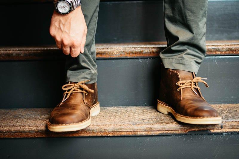 Model wearing jack mason watch and clarks desert boot adjusting pant cuff