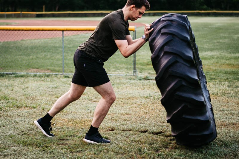 model flipping tire in kore workout shorts from vuori