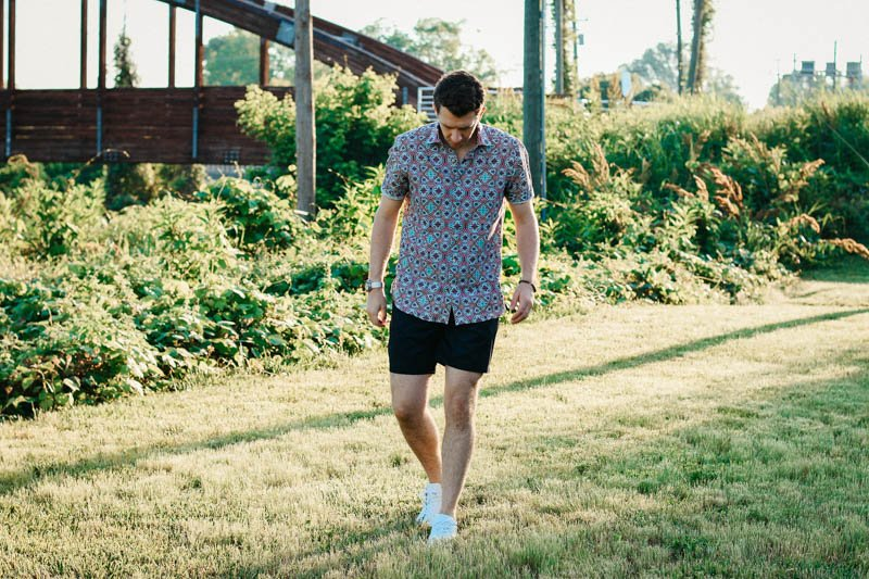 model walking toward camera in grass wearing robert graham shorts shirt and white minimalist sneakers