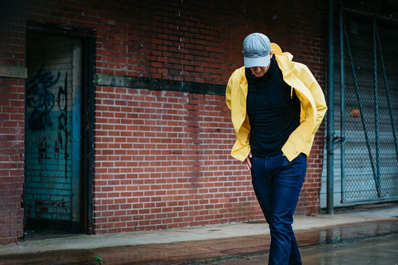 model wearing rains yellow waterproof jacket and everlane hat in the rain