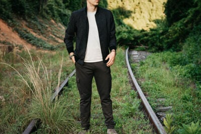 Best Bomber Jackets for Men Male model wearing Paige Bomber Jacket and Cargo pants on railroad track outside