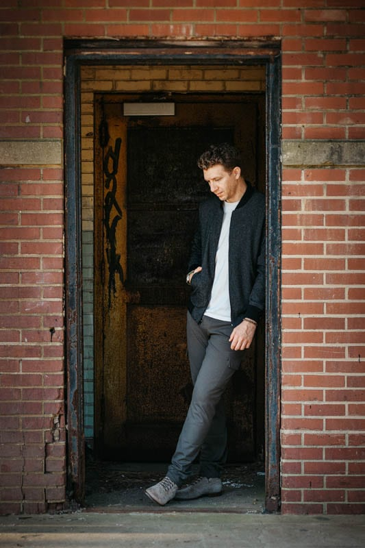 model leaning on brick doorway wearing paige jeans and bomber jacket