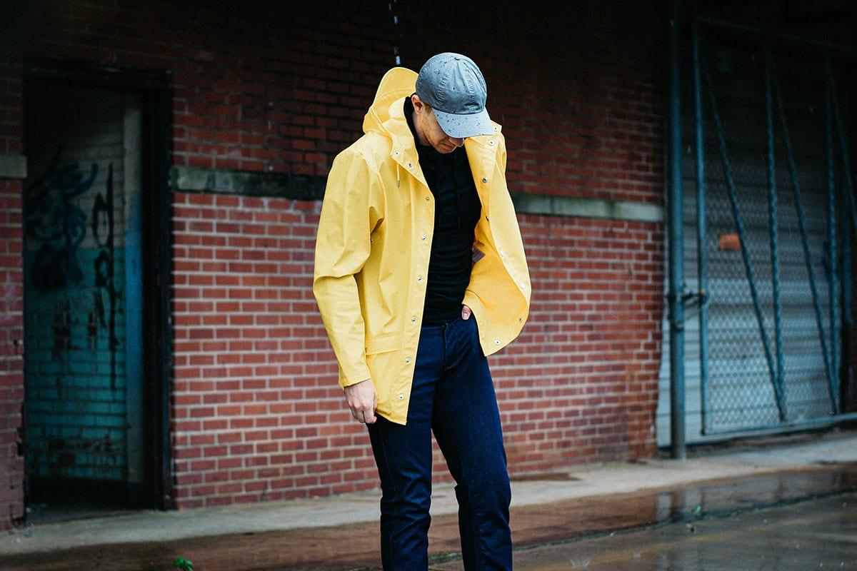 model wearing a yellow rains waterproof jacket and raw denim jeans