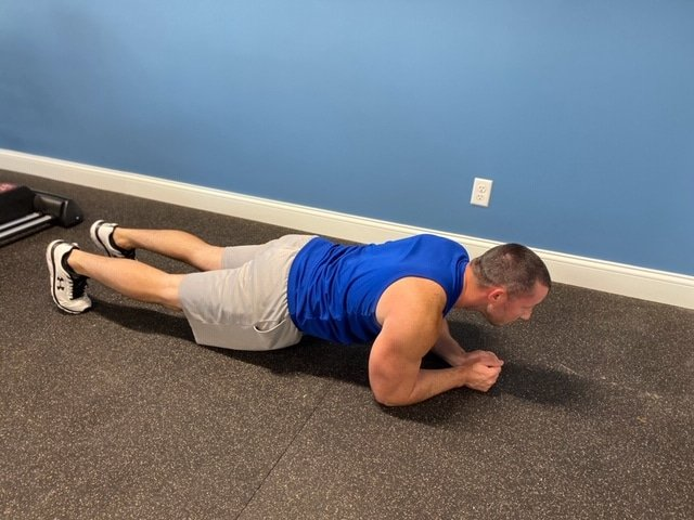 Fitness model performing plank exercise indoors