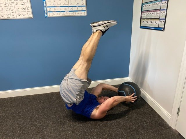 Fitness model performing reverse crunch leg raises indoors