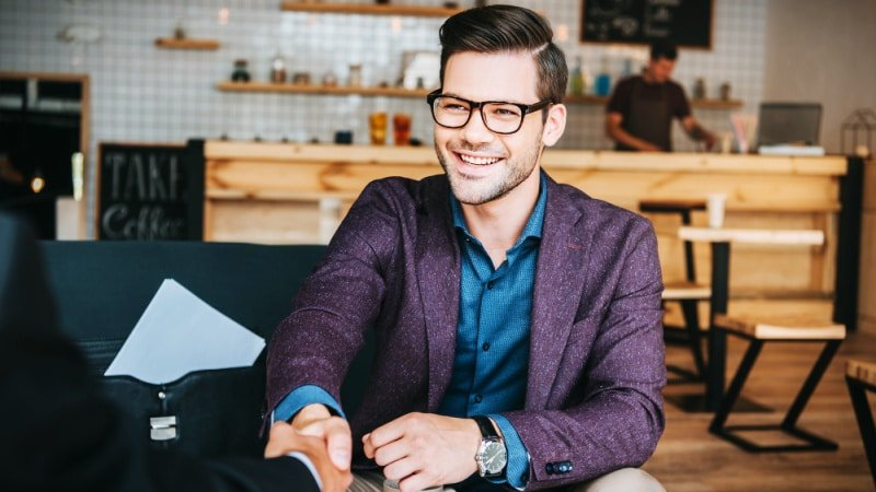 Attractive Business Man with Glasses and Wearing a Suit Shaking Hands in Cafe
