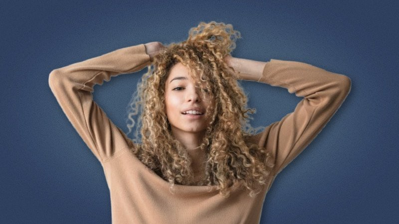 Attractive woman playing with her curly hair on blue background 1