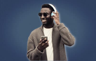 Best Podcasts for Men African American Model Smiling While Wearing Headphones and Phone