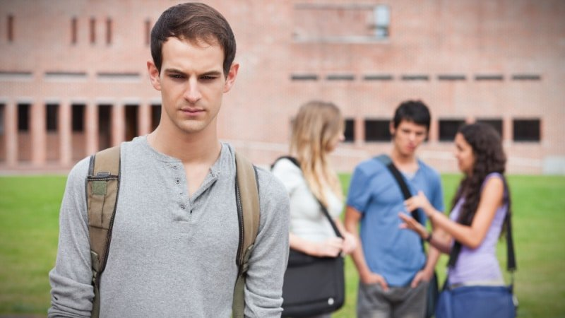 Lonely Student Gamma Male with Friendship Circle Behind Him in Background