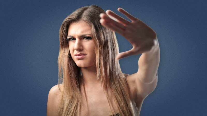 Pretty girl putting up her hand in rejection on plain background 1