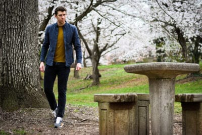 model sitting at bench with everlane tread sneakers blossoming trees