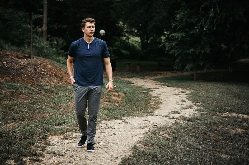 model walking along dirt path wearing rhone notch tee