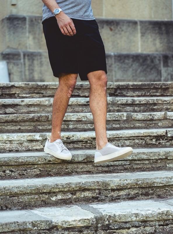 Man in grey Soludos descending staircase