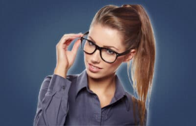 Signs a Female Coworker Likes You Attractive Woman With One Hand on Glasses Looking at Camera and Smiling