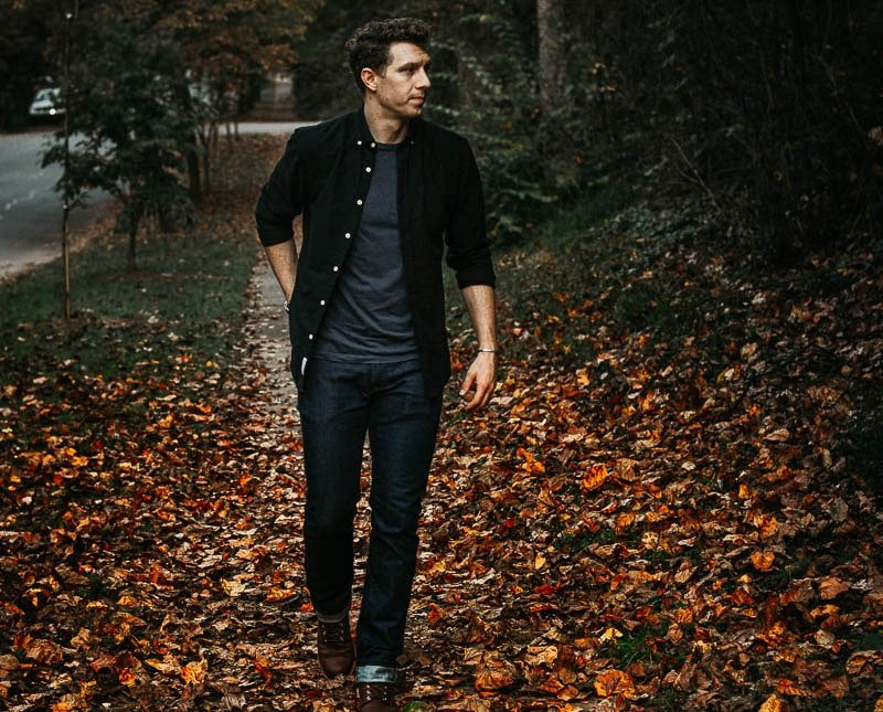 model in black oxford and blue tshirt on red fall leaves