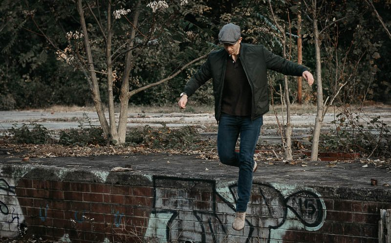 model jumping down from wall with jeans hat and bomber jacket