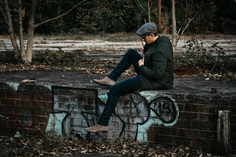 model sitting on wall in green frank and oak bomber jacket and hat