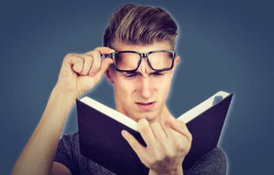 Best Dating Books  Young Man in Glasses Reading a Navy Book and Shocked at What Hes Reading