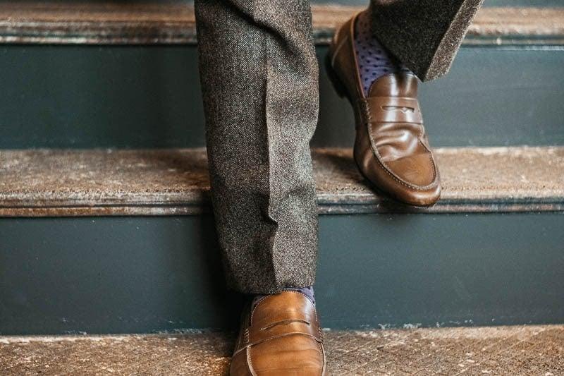 Gentlemans Box Classic walking down steps in brown suit purple socks