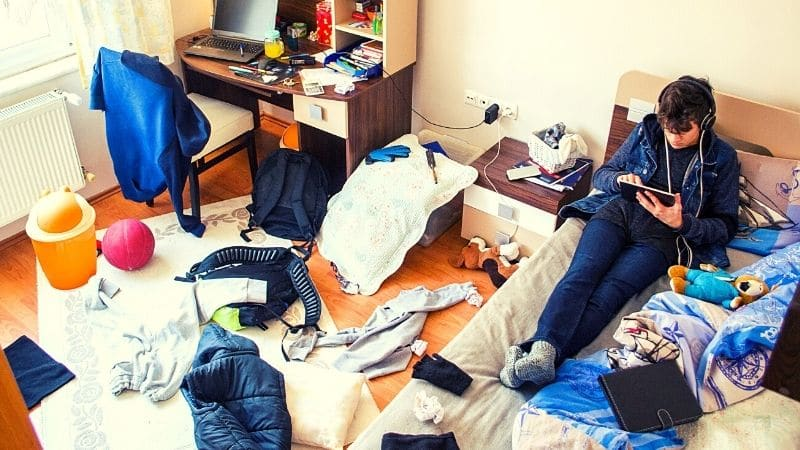 Man on Bed with Messy Bedroom