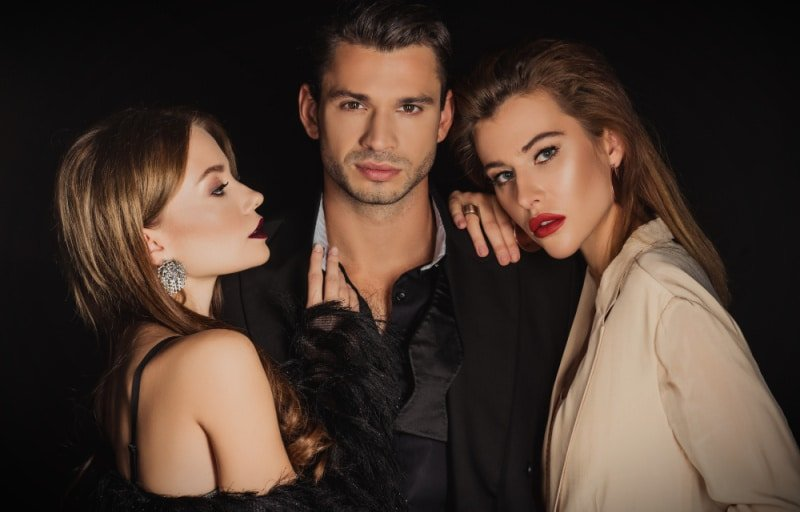 Attractive man with two beautiful women on black background