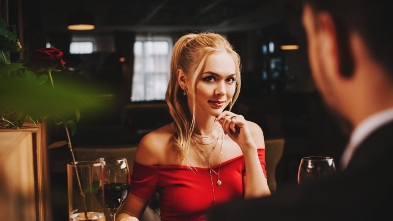 Attractive woman flirting with attractive man in suit at dinner