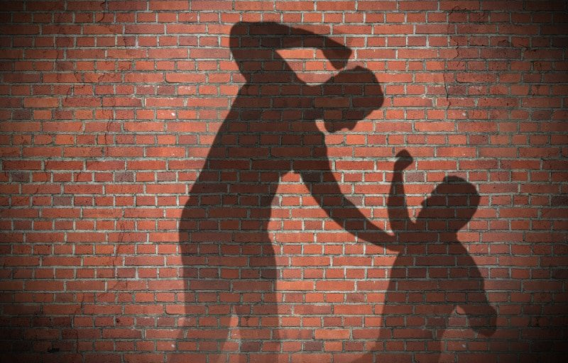Shadow on a brick wall of a Man beating up another man