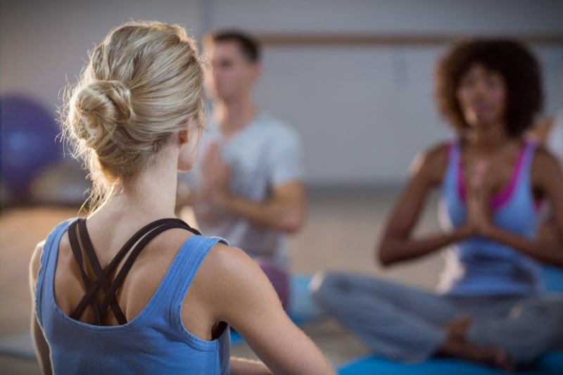 Female instructor teaching yoga class guy and girl