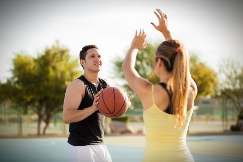 Man playing basketball outside with woman defending