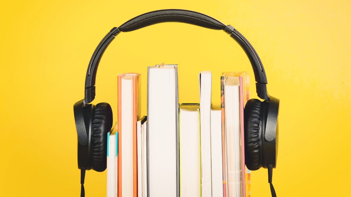 Audible Review Headphones Sitting Over the Top of Books