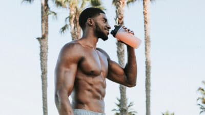 Best Protein Shake Recipes for Muscle Gain Muscular Black Man Smiling and Drinking Protein Shake Outside